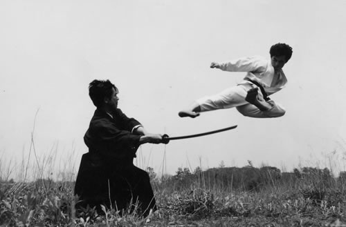 Tomosaburo Okano with Sword in Hand with student Toyotaro Miyazaki performing flying Side Kick